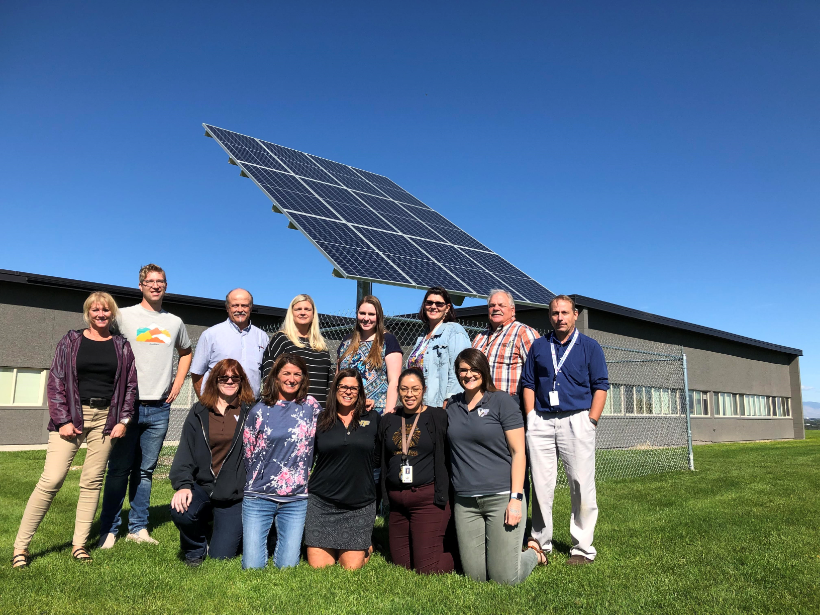 teachers standing in front of a demonstration solar array